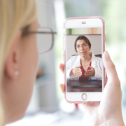 A woman looking at her phone, which shows a doctor on in a telehealth appointment